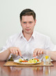 Handsome man eating with fork and knife