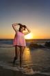 Ragazza al tramonto sulla riva del mare
