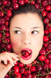 Young woman portrait biting a cherry surrounded by cherries.