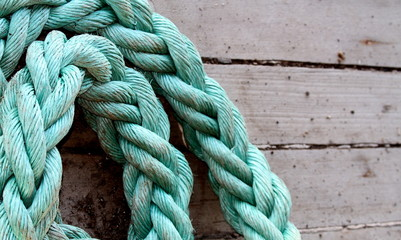Old texture of wooden boards with green ship rope