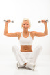Fitness woman lifting dumbbells sitting white floor