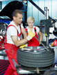 Car mechanic with tyre lever is fitting a summer tyre
