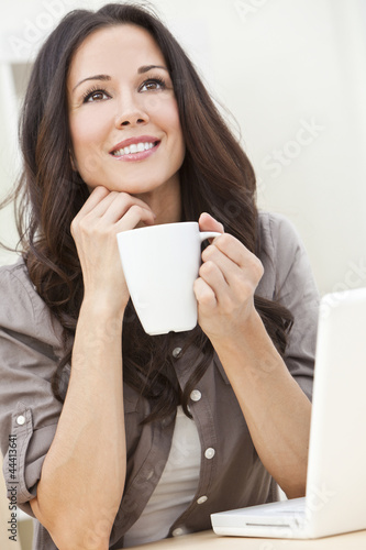 Beautiful Woman Using a Computer and Drinking Tea or Coffee