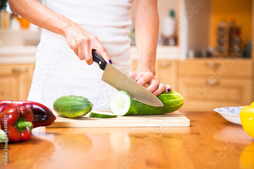 Human hands cutting vegetables for salad