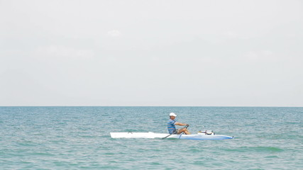 A man kayaking in the sea on a sunny day
