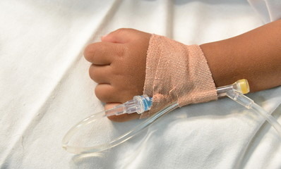 Hand of sick child, intravenose set infusion.
