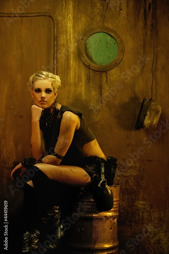 Blond girl in a bunker sitting on a barrel