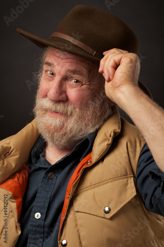 Friendly elderly man smiles and tips his hat