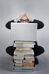 Verzweifelter Mann hinter Laptop Bücherstapel