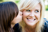 Young daughter kissing mother's cheek