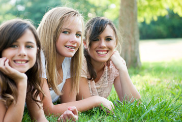 Three young girls sitting in the grass