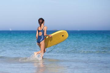 Mädchen geht mit Surfbrett ins Meer
