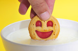 someon soaking a smiley-shaped cookie in milk