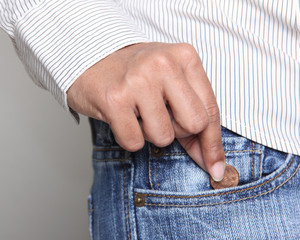 person taking a penny from jean pocket