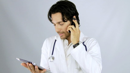 Doctor talking on the phone while looking tablet