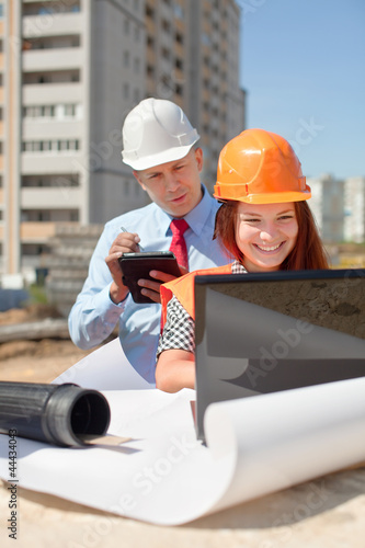Two architects works in front of building site