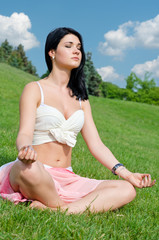 Serene girl meditating on grass