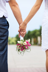 Newlyweds holding hands and carrying bride's bouquet