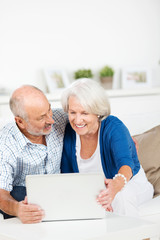 glückliches älteres paar schaut auf den laptop