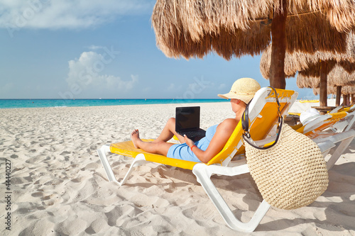 Woman with laptop relaxing on the deckchair at the Caribbean sea