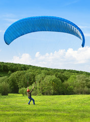 Paraglider. Man with parachute struggling with the wind.