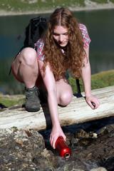 Junge Frau schöpft Wasser