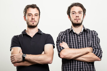 Two Serious Twins with Arms Folded
