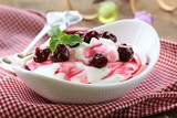 dairy dessert with sweet  sauce and cherries
