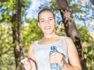Happy girl in forest holding bottle of water