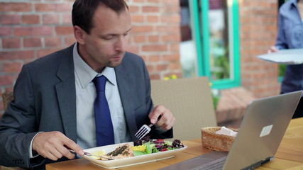 Businessman working with businesswoman during lunch