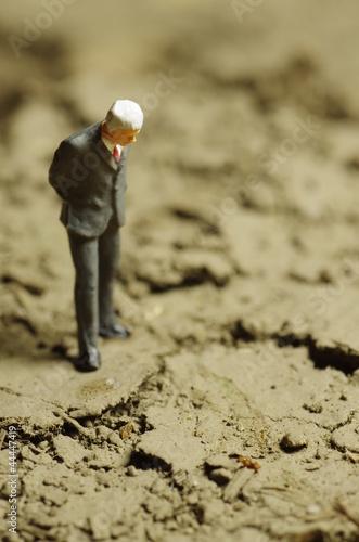 地面を見る男