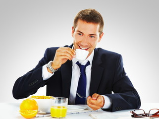 busy businessman using his laptop while having breakfast