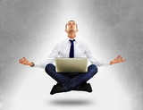 Businessman sitting in yoga position