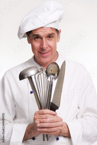 Cocinero chef sujetando utensilios de cocina cocinando de for Utensilios de chef