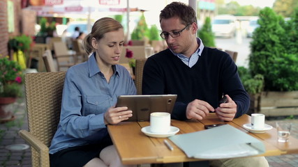 Business people working with documents and smartphone in cafe