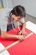 Dressmaker Measuring Red Fabric