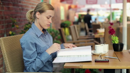 Businesswoman reading documents and drinking coffee in cafe