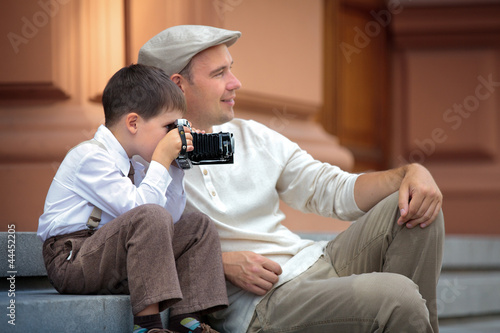 Father and little son holding retro camera in city