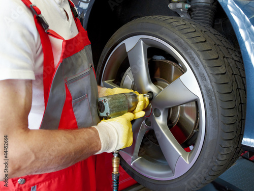 To fit a summer tyre with impact screwdriver on a service lift