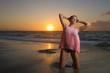 Ragazza in posa sulla riva del mare al tramonto