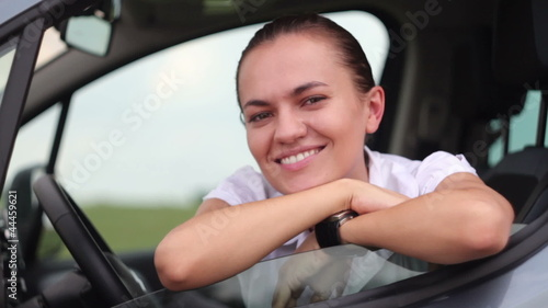 Portrait of young smiling woman sitting in the car