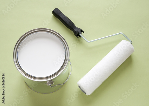 Can of white paint and roller on green background