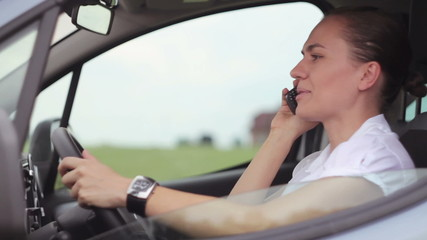 Businesswoman in the car using cell phone and checking the time