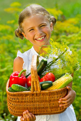 Vegetable garden - lovely girl with picked vegetables in basket