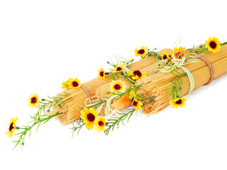 Uncooked Italian spaghetti decorated with yellow flowers isolate