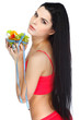 Portrait of a pretty young woman eating vegetable salad isolated