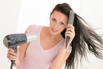 Woman blow-drying hair using round hairbrush