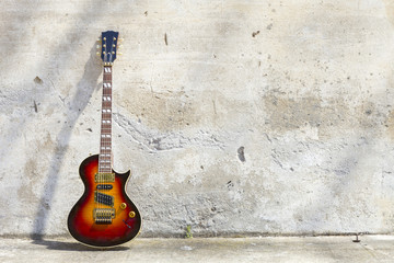 electric guitar in front of a vintage wall