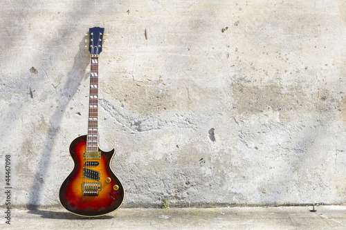 Leinwanddruck Bild electric guitar in front of a vintage wall