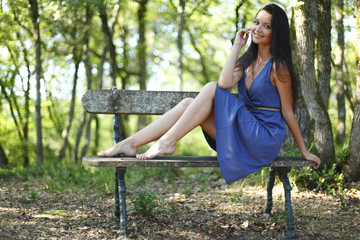 Young woman sitting on the bench in park